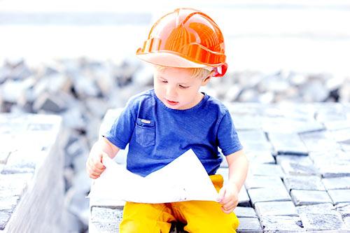 dziecko w kasku z projektem domu w rękach