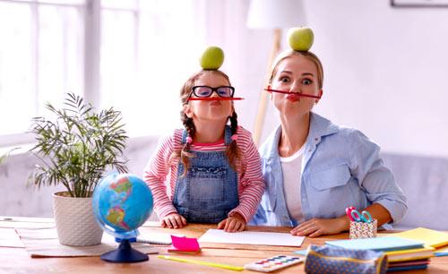 niania bawiąca się z dziewczynką z jabłkami na głowie