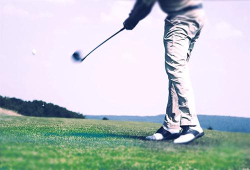 nogi człowieka uderzającego kijem piłeczkę golfową