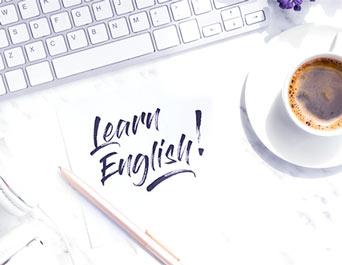 napis learn english na blacie z kawą i klawiaturą