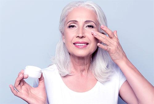 kobieta smarująca zmarszczki pod oczami kremem przeciwzmarszczkowym